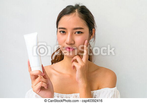 beautiful asian woman using a natural skin care product, moisturizer or lotion. isolated