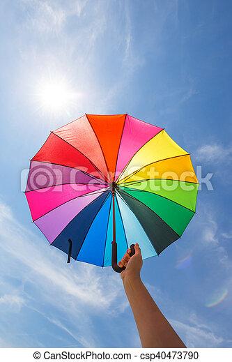 open colorful rainbow umbrella on blue sky background, vintage look
