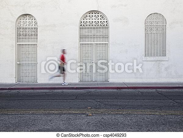 Fast paced man runs down city street. - csp4049293