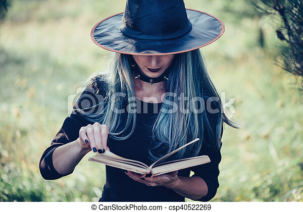 Young woman in costume of witch reading a book of magic outdoor, close-up, front view. Theme of Halloween and magic