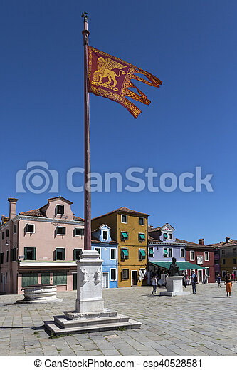 The Venetian flag on the island of Burano in the Venetian Lagoon, northern Italy. It is situated near Torcello at the northern end of the Lagoon, and is known for its lace work and brightly coloured homes.