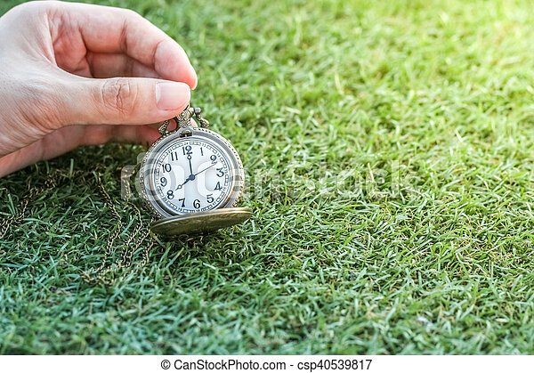 Hand holding vintage pocket gold watch with green grass, abstract for time concept with copy space