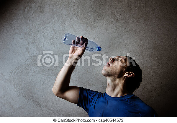 Muscle man drinking water from blue plastic bottle on gray wall backdrop