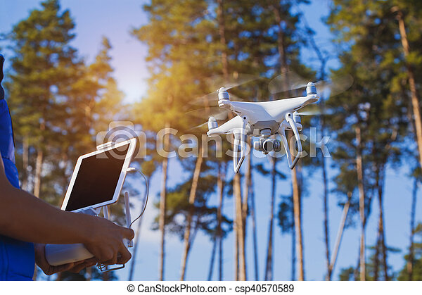 Man controls quadrocopter flight. Flying the copter in the forest. Remote control in a man\'s hands.