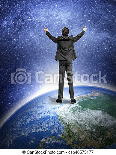 Man in a suit standing on the Earth planet and on the background of the night sky. Science, Astronomy concept. Elements Of This Image Furnished By Nasa.