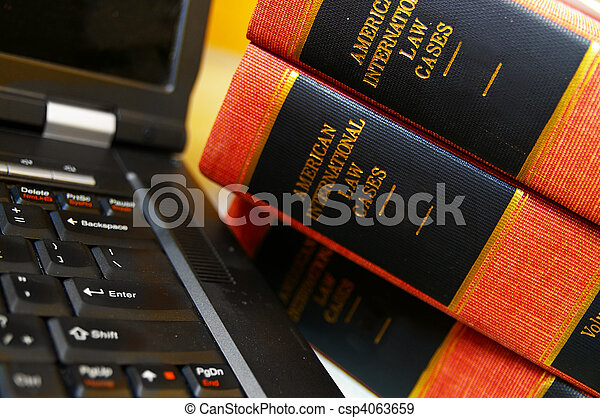 laptop computer and a stack of law books - csp4063659