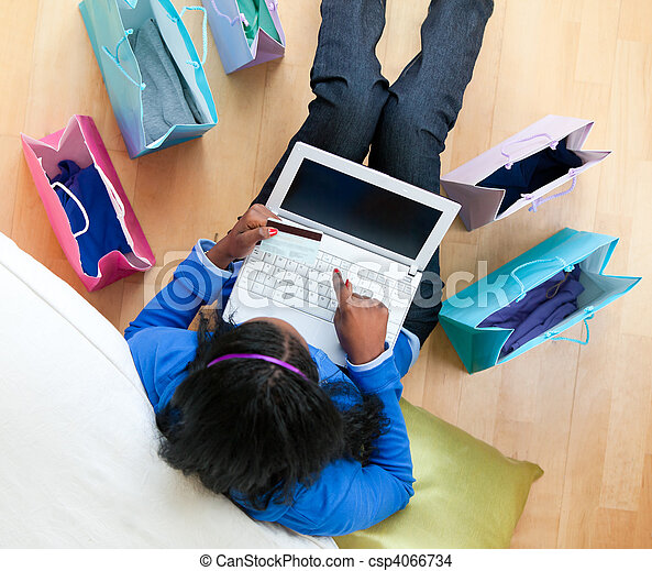 Pretty afro-american teenager using a laptop sitting between shopping bags on the floor in the living room - csp4066734