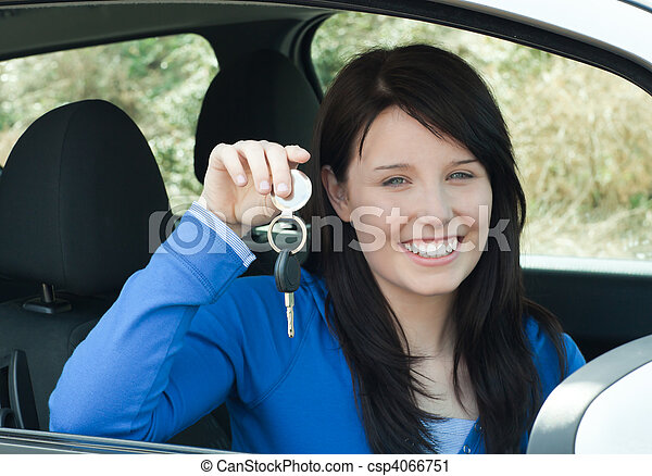 Radiant teenager holding car keys sitting in her new car - csp4066751