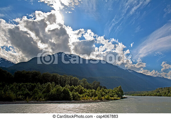 View of the Squamish River at Brackendale Eagles Provincial Park in British Columbia, Canada with sun flare behind dramatic clouds - csp4067883