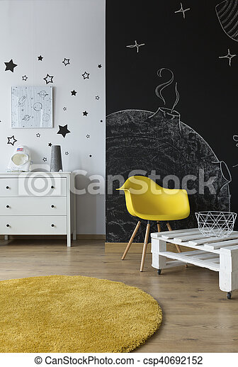 Light room with floor panels, simple furniture, stars wall stickers and blackboard wall