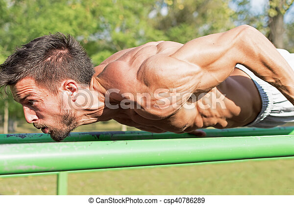 Young Athlete Working Out in an Outdoor Gym. Street Workout Exercises. Tense Muscles.