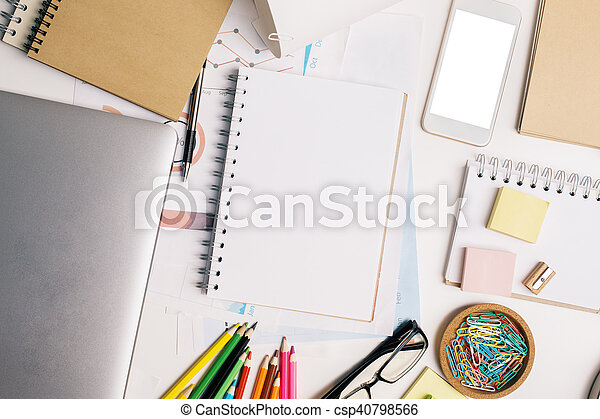 Top view of office workplace with blank spiral notepad, white cellphone, closed laptop and colorful supplies. Mock up