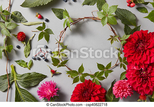 round frame wreath pattern with flower buds, branches and leaves isolated on black background. flat lay, top view with space for text