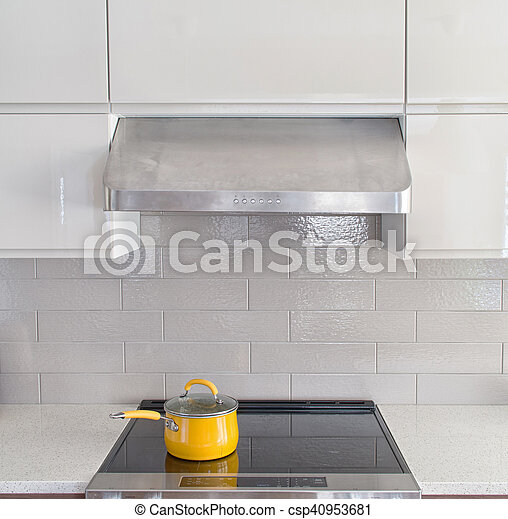 Modern kitchen range with yellow cooking pot on it