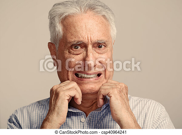 Scared afraid elderly man portrait over gray wall background.