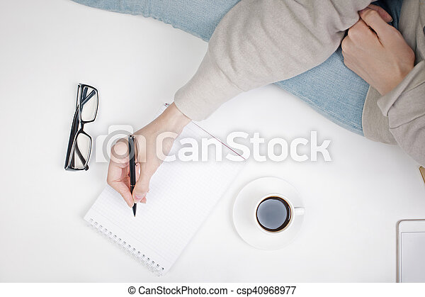 Top view of girl\'s hand writing in notepad placed on white surface with coffee cup and other items. Mock up