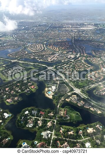 Town in aerial view from the airplane with cloud and blur, Weston, Florida