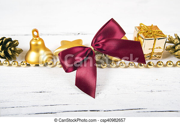 Brilliant gold baubles and cones like christmas decoration. Yellow balls ribbon, gift, red bow and tinsel isolated on white background.