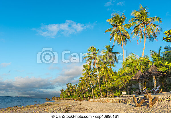 Tropical beach background from Anda White Beach at Bohol island with beach chairs on the white sand beach with cloudy blue sky and palm trees. Travel Vacation