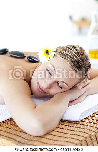 Close-up of a caucasian woman with hot stone on her back and closed eyes in a spa center - csp4102428