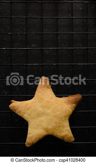 Overhead shot of a single, imperfect star shaped Christmas biscuit, freshly baked and placed on a black wire cooling rack.