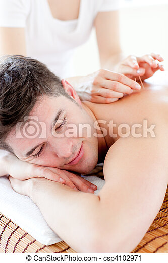 Charming young man in an acupuncture therapy in a Spa center  - csp4102971