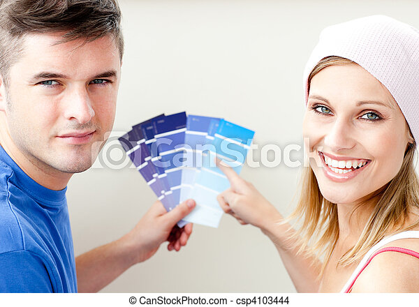 Cheerful couple with color samples for painting a room  - csp4103444