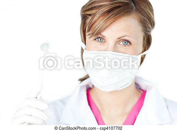 Female dental surgeon wearing a mask - csp4107702