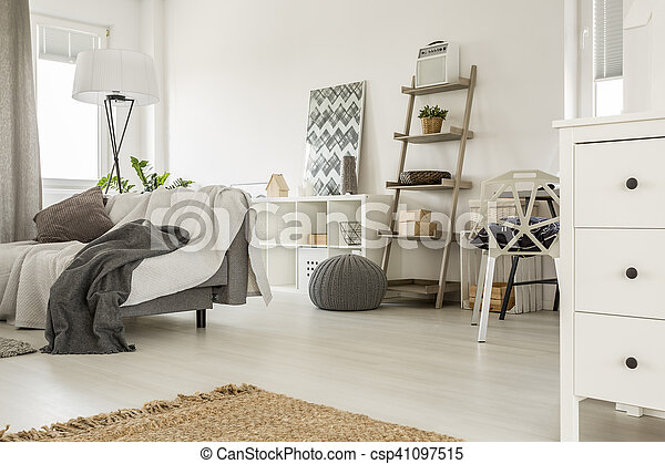 Spacious home interior in white with sofa and wooden furniture