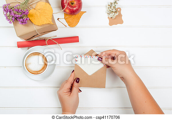 Female hands hold gift card. Gift boxes, a cup of cappuccino on autumn background.