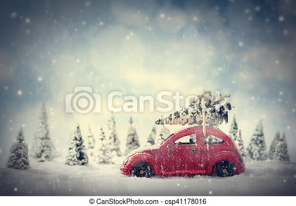Retro toy car carrying tiny Christmas tree. Fairytale, miniature scenery with snow and forest.