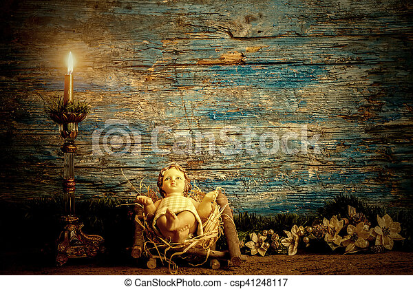 Christmas card, baby Jesus in his crib and vintage candle in rustic wooden background with copy space