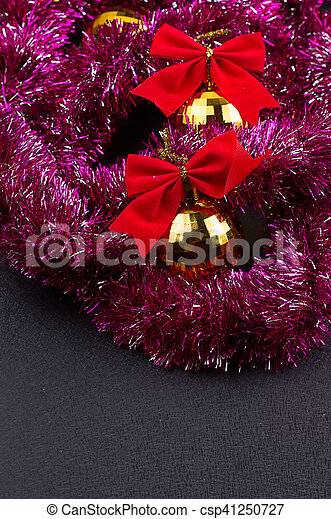 Beautiful Christmas decoration. Gold Christmas balls and bright sparkling golden tinsel with red bows on black background