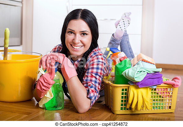 Pretty young cleaning lady lying on the kitchen floor with lot of cleaning supplies and tools. House cleaning concept