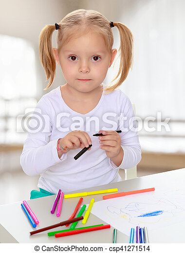 The concept of pre-school education of the child among their peers . in gaming room with a large arched window.Pretty little blonde girl drawing with markers at the table.