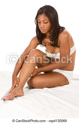 Beautiful black girl applies moisturizer on legs - csp4130069