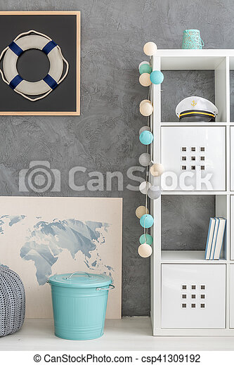 Modern home interior with grey decorative wall finish, nautical decor and white storage unit