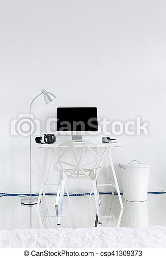 Home work station with computer on a desk, lamp and modern chair