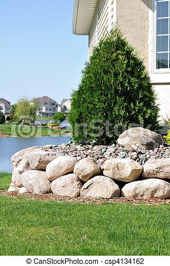 Stone Retaining Wall and Evergreen Shrub - csp4134162