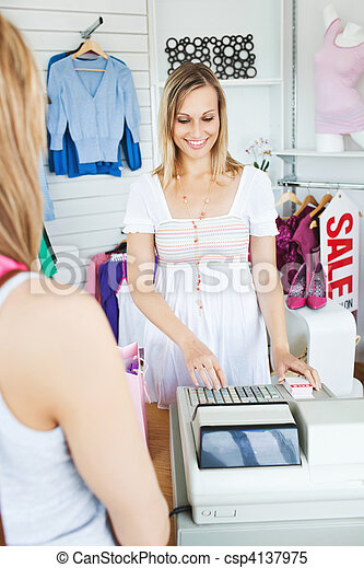Positive saleswoman standing behind the counter using the cash register in a clothes store - csp4137975