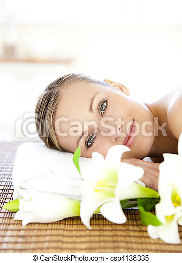 Portrait of a charming woman lying on a massage table smiling at the camera in a health spa - csp4138335