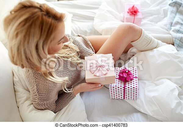 holidays, birthday, morning and people concept - close up of happy young woman gift boxes or presents in bed at home bedroom