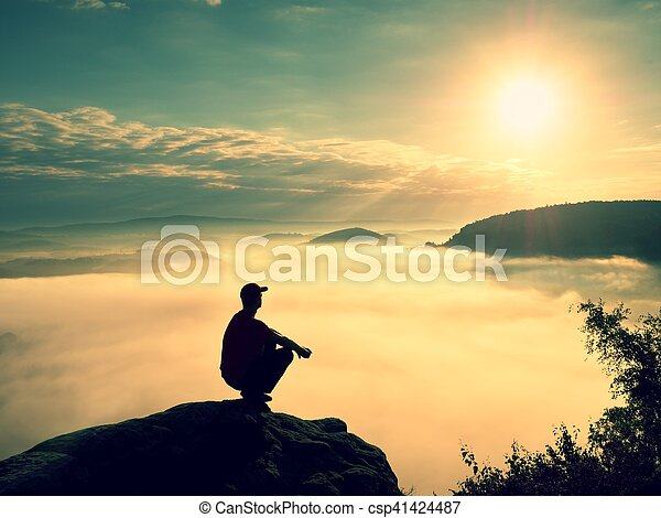 Moment of loneliness. Man sit on rock and watching into colorful mist and fog in valley. Man hiking. Sad person relaxing.Spring nature. Fall mountain valley. Tired man relaxing.