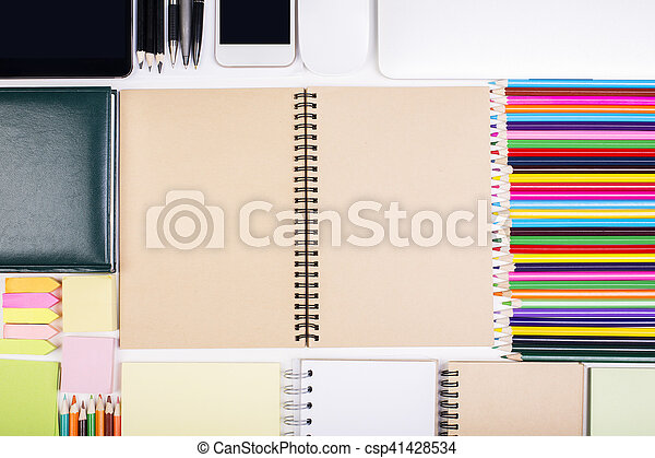 Top view of desktop with blank spiral notepad, colorful suppliles and smartphone. Mock up