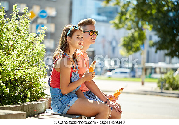 fast food, summer and people concept - happy teenage couple eating hot dogs sitting on city street bench