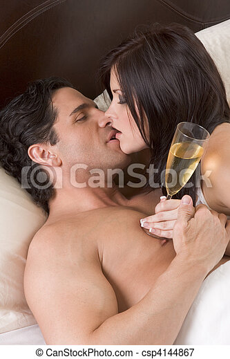 Loving young sensual couple with Champagne in bed - csp4144867