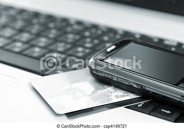 Credit cards and mobile phone on the notebook - csp4149721