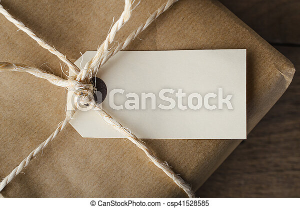 Overhead close up of a blank parcel label, tied with string to a package wrapped in plain brown paper.