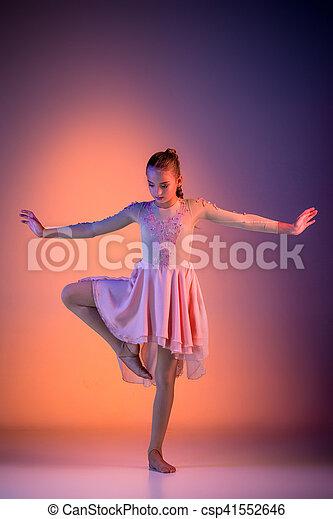 The female teen modern ballet dancer on orange studio background