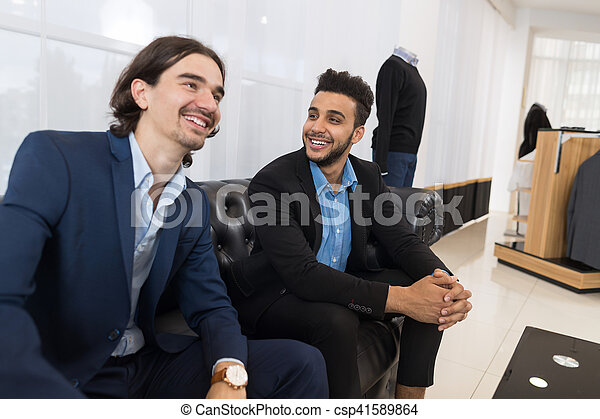 Two Young Handsome Business Man Sitting On Coach In Retail Store Speaking Shopping, Elegant Businessman Choosing Formal Wear